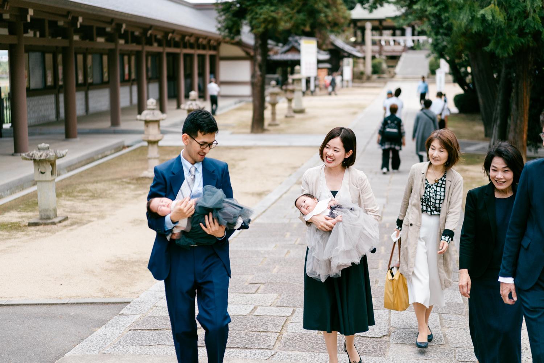 お宮参り中に神社の境内を歩くご家族の姿