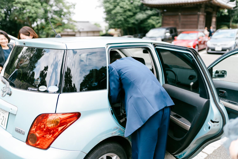 車のチャイルドシートに赤ちゃんを載せているところ